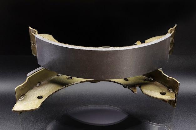 Pastiglie per freni a tamburo con riflesso sulla superficie su sfondo nero. riparazione dell'impianto frenante dell'auto.