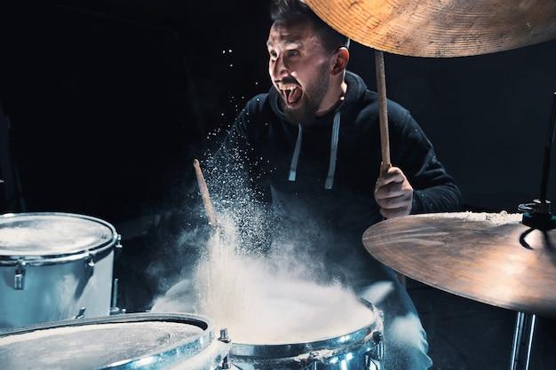 Batterista che prova alla batteria prima del concerto rock. uomo che registra musica su batteria in studio con effetto spettacolo sotto forma di farina