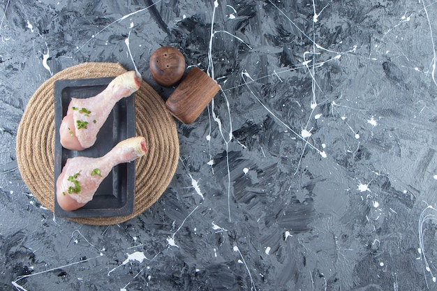 Bacchette su un piatto di legno sul sottopentola, sullo sfondo di marmo.