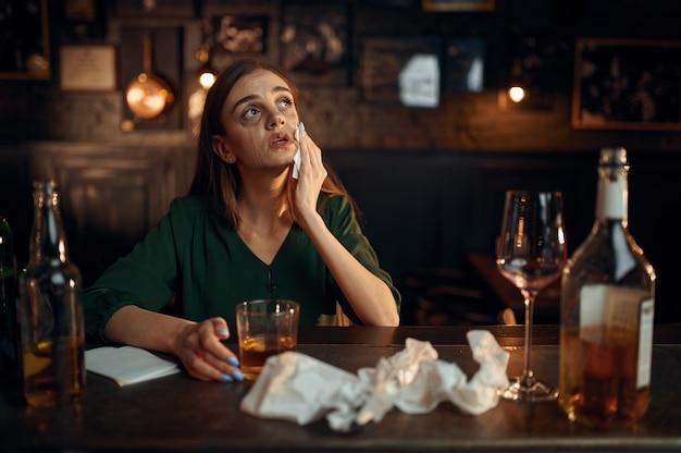 Donna depressa ubriaca al bancone del bar