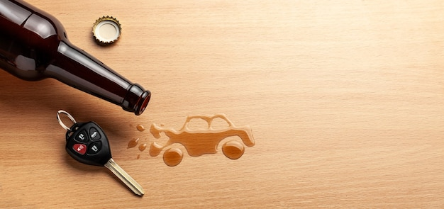 Guida in stato di ebbrezza. incidente con un'auto rotta dall'alcol. bottiglia di birra e chiavi della macchina. macchina rotta.