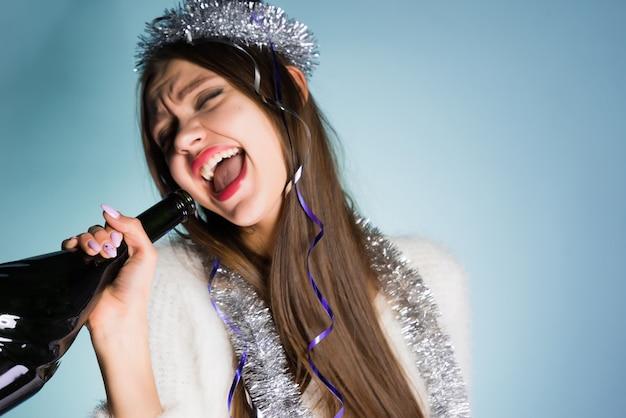 La donna felice ubriaca in cappello festivo tiene una bottiglia in mano