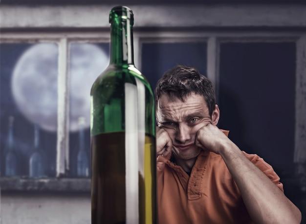 L'uomo ubriaco guarda la bottiglia di vino di notte