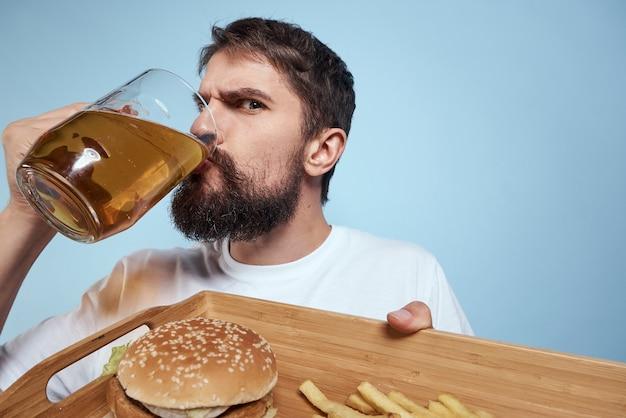 Uomo ubriaco in posa con una birra e fast food
