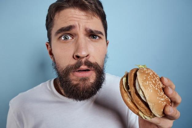 Uomo ubriaco in posa con un hamburger