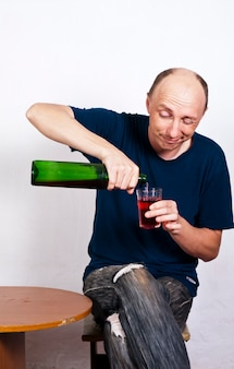 Uomo ubriaco che versa vino in un bicchiere