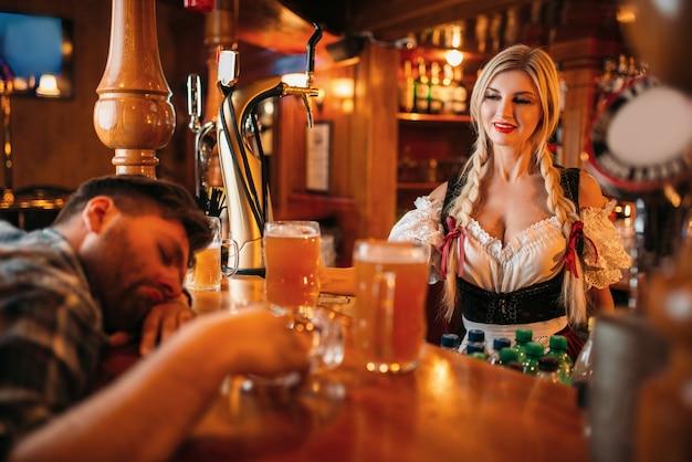 Uomo ubriaco che dorme al bancone con boccali di birra nel pub