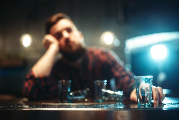 Uomo ubriaco dorme al bancone del bar, dipendenza da alcol