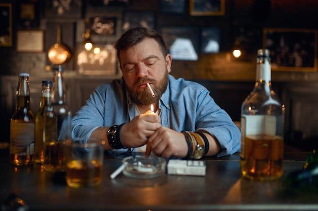 Uomo ubriaco fuma una sigaretta al bancone del bar
