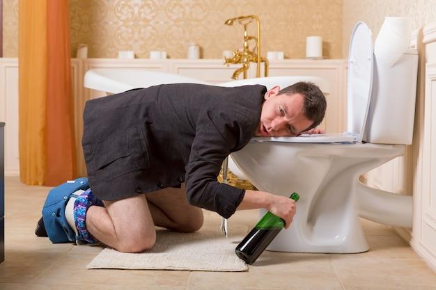 Uomo ubriaco con una bottiglia di vino malato nella tazza del gabinetto
