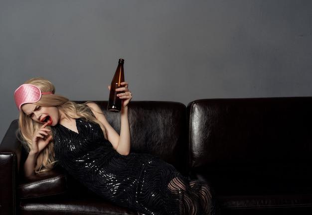 Donna ubriaca sul divano divertente emozioni rossetto rosso alcool sfondo scuro