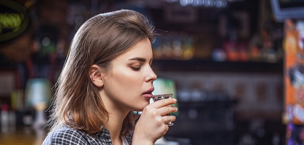 Donna ubriaca con in mano un bicchiere di whisky o rum. donna in depressione. giovane bella donna che beve alcolici. bicchiere da whisky scozzese isolato al bar o al pub in abuso di alcol e concetto alcolico