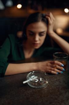 La donna ubriaca fuma una sigaretta al bancone del bar