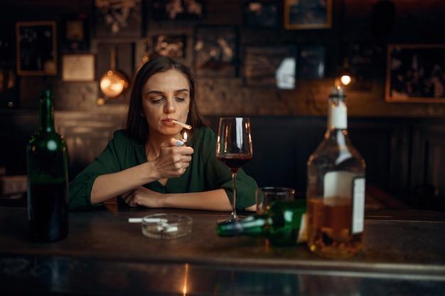 Donna ubriaca fuma una sigaretta al bancone del bar