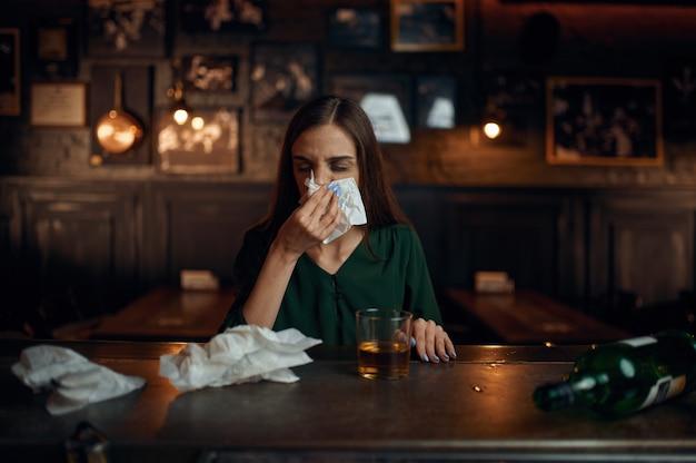 Donna ubriaca si pulisce il naso con un tovagliolo al bar