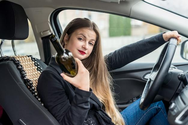 Donna ubriaca con una bottiglia di alcol che si siede in macchina