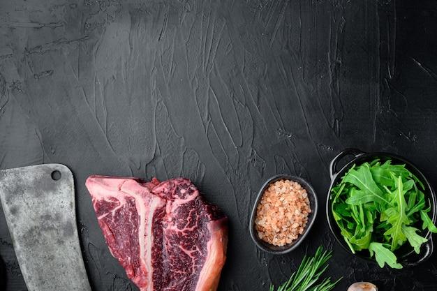 Bistecca di carne cruda t-bone o porterhouse stagionata a secco con erbe e sale set, su pietra nera