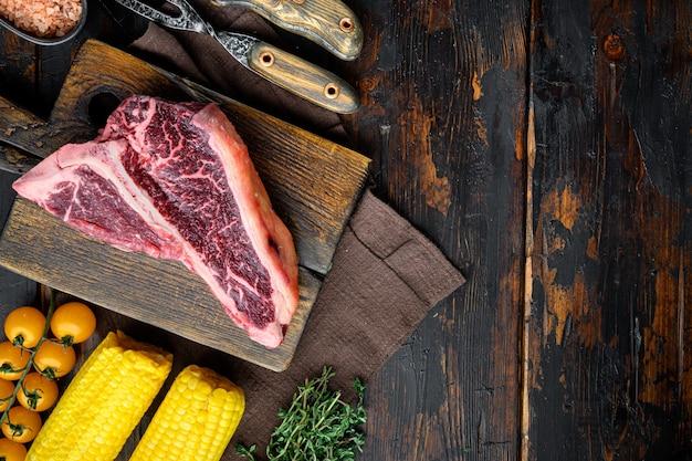 Bistecca di carne di manzo cruda stagionata a secco o porterhouse con erbe e sale, su vecchio tavolo di legno scuro