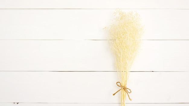 Asciughi il fiore del respiro del bambino su una tavola di legno bianca
