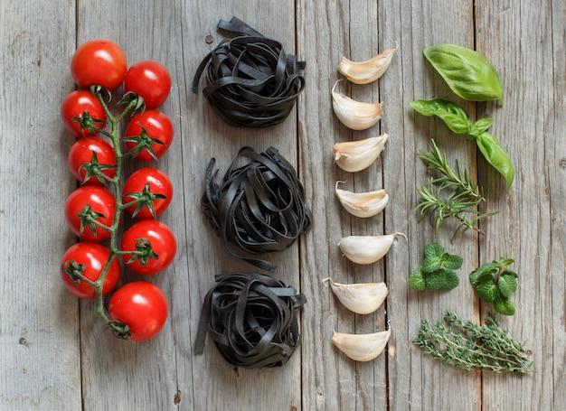 Tagliatelle nere secche con pomodorini, aglio ed erbe aromatiche su un tavolo in legno vista dall'alto