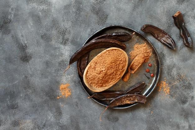 Carruba secca in polvere e baccelli vista dall'alto su un tavolo grigio