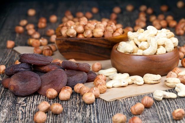 Anacardi secchi, nocciole e altra frutta secca su un vecchio tavolo di legno e in una ciotola di legno, un mucchio di anacardi e nocciole, altri prodotti alimentari sul tavolo e in un piatto di legno durante i pasti