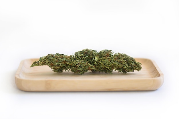 Germogli di piante secche cbd su un vassoio di legno con uno sfondo bianco
