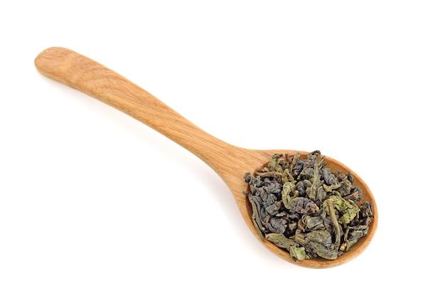 Foglie di tè cinesi secche su cucchiaio di legno su sfondo bianco, vista dall'alto