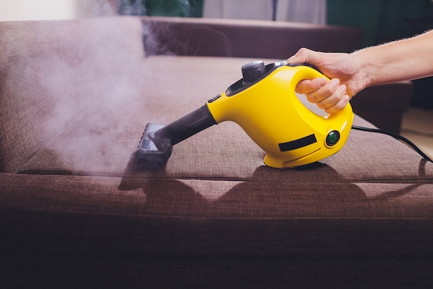 Impiegato del lavasecco che rimuove sporcizia dalla mobilia in piano, primo piano. Foto Premium