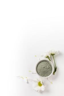 Argilla blu cosmetica asciutta in ciotola bianca del fronte con i fiori su fondo bianco