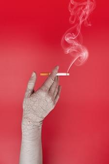 Mano secca e screpolata che tiene una sigaretta fumante, effetti negativi del fumo sulla pelle.