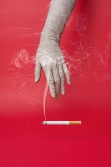 Mano secca e screpolata e una sigaretta fumante su sfondo rosso.