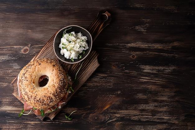 Prosciutto crudo e ricotta bagel per colazione su uno sfondo di legno scuro, panino con prosciutto e microgreens, vista dall'alto.