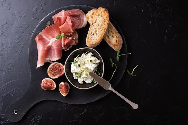 Prosciutto crudo stagionato con fette di pane su sfondo nero, prosciutto italiano antipasto con frutta e formaggio, primo piano.