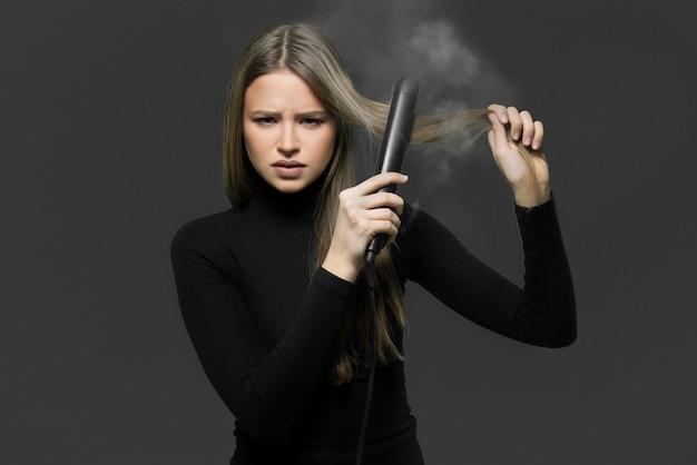 Capelli secchi danneggiati bruciati con il concetto di ferro da stiro. ragazza giovane con capelli ferro bruciando i suoi capelli.