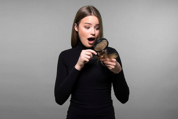 Capelli secchi danneggiati, doppie punte, concetto di cura dei capelli. ragazza che controlla i suoi capelli con una lente d'ingrandimento.