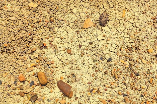 Terra secca con crepe e pietre, terra crepata a causa della siccità. uno sfondo vintage per il design e la creatività può essere utilizzato come copertina per opuscoli o sfondi