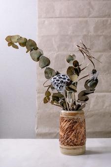 Ramo di fiori secchi, eucalipto e ramoscelli in vaso in ceramica marrone sul tavolo in marmo bianco con parete grigia dietro.