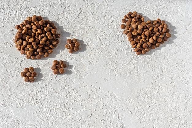 Cibo secco per cani e gatti a forma di cuore ea forma di impronta su fondo in gesso bianco, copia spazio, vista dall'alto. il concetto di amore per gli animali domestici. concetto di cibo per animali domestici sano