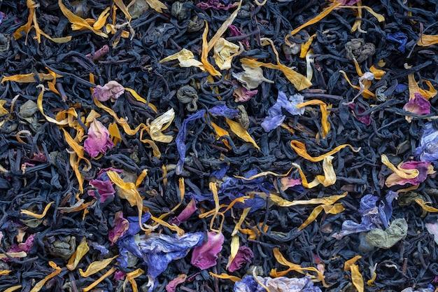 Tè alle erbe secche con frutta e petali di fiori come sfondo, vista dall'alto. concetto di alimentazione sana