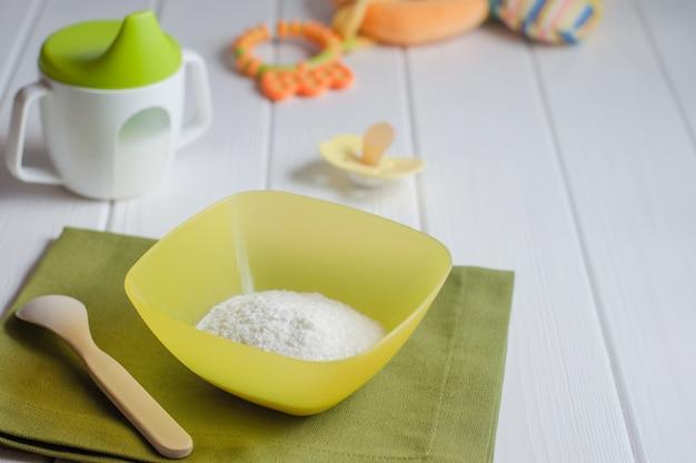 Porridge di riso istantaneo asciutto su fondo di legno bianco