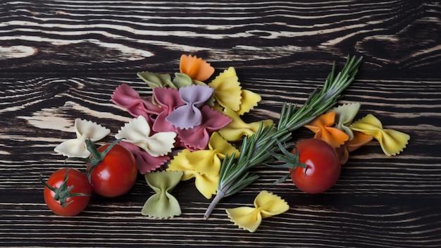 Farfalle o fiocchi di pasta italiana secca con pomodori e rosmarino su fondo di legno scuro