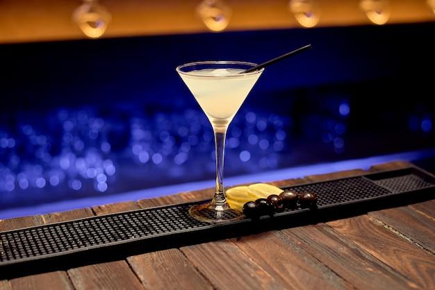 Un cocktail martini secco con ghiaccio si trova su un bancone bar pronto per essere servito a un cliente.