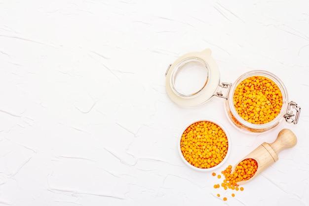 Lenticchie arancioni secche in barattolo di vetro. una preziosa fonte di proteine per una sana alimentazione vegana.
