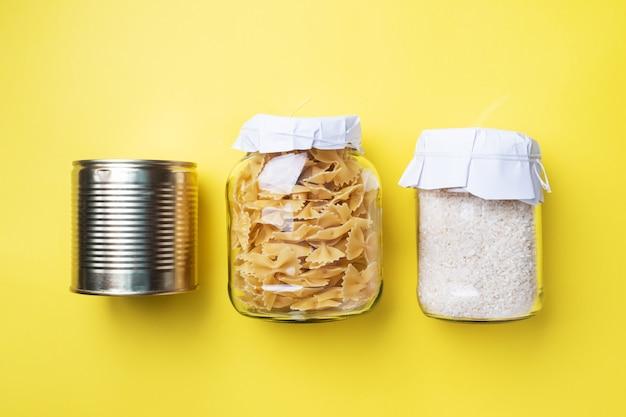 Pasta secca e riso in un barattolo di vetro e lattine con cibo in scatola. concetto di conservazione degli alimenti, donazioni.