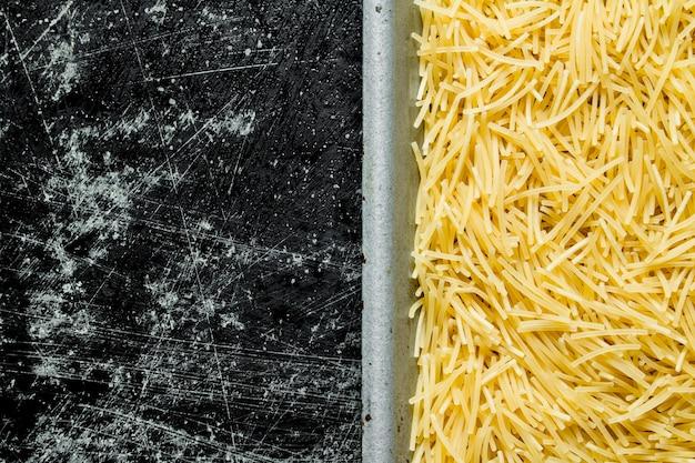 Vermicelli di pasta secca sulla tavola rustica