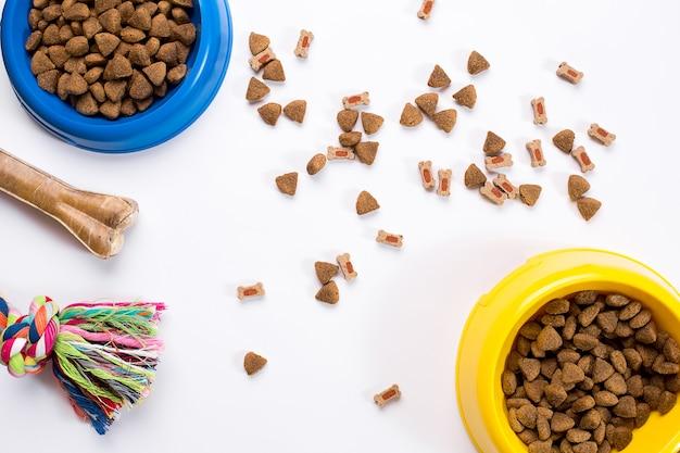 Cibo secco per animali in ciotola e giocattoli per cani su sfondo bianco vista dall'alto