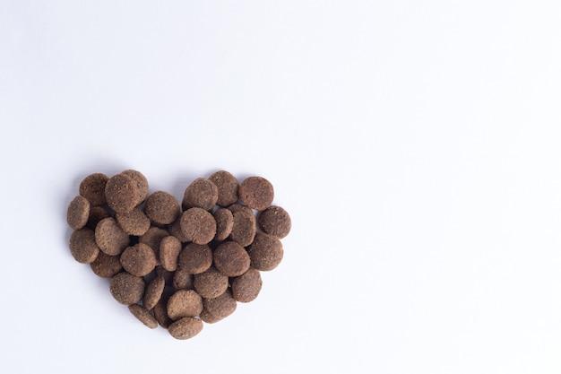 Alimento secco per cani e gatti a forma di cuore isolato su sfondo bianco, copia spazio, vista dall'alto. il concetto di amore per gli animali domestici. concetto di cibo per animali domestici sano