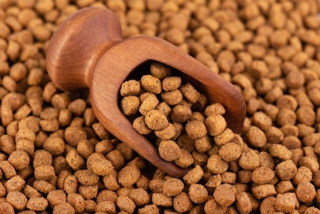 Cibo secco per animali domestici in cucchiaio di legno. pila di mangimi per animali in granuli