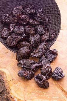 Prugne secche che fuoriescono da una tazza scura su un legno
